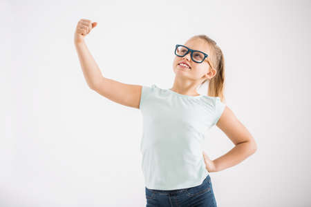 Smart girl with glasses standing like a superhero against white background