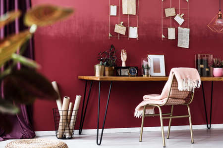 Pink blanket on metal chair at desk with gold clock and plants in cozy, cherry home office interior with basket