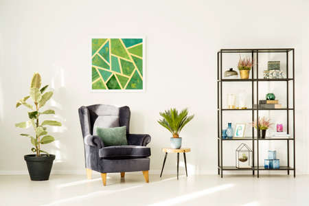 Bright living room interior with grey armchair and emerald picture in the center 版權商用圖片