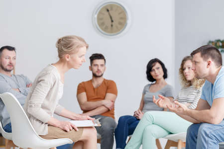 Young therapist talking to a man during therapy, surrounded by a support group
