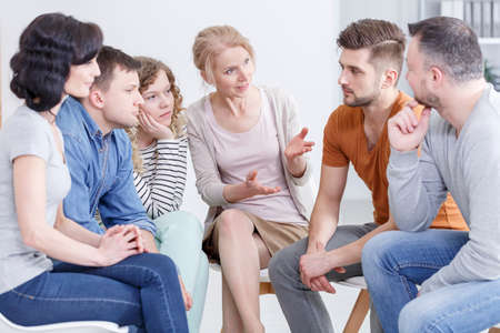 Female therapist talking to her patients during a support meeting