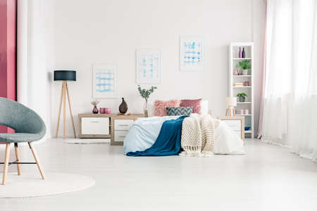 Simple, white themed, scandinavian bedroom interior with king size bed, posters, armchair, bookshelf and lamp Stockfoto