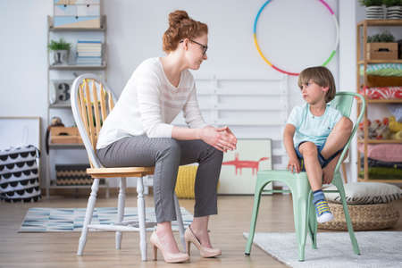 Psychologist talking to a boy sitting on a chair with an angry face