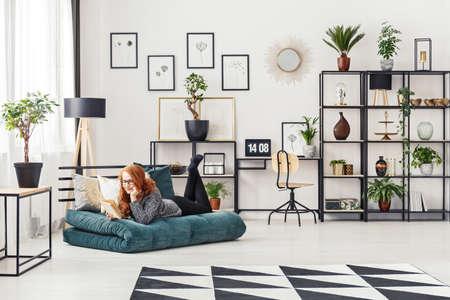 Donna dello zenzero che legge un libro mentre trovandosi su un materasso in un interno moderno del salone