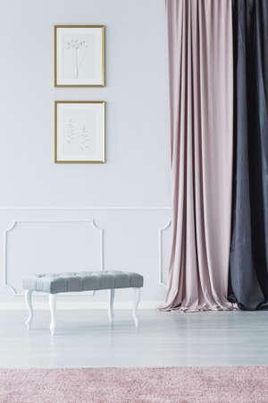Elegante asiento tapizado de estilo banco, cortinas largas y alfombra rosa pálida en un lujoso interior blanco en el pasillo