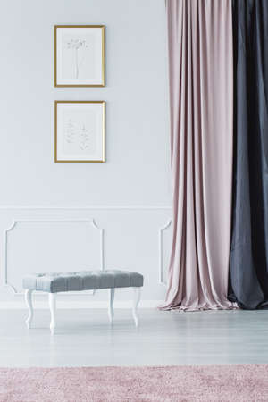 Elegant, upholstered, bench style seat, long curtains and pale pink rug in a white, luxurious hallway interior