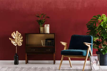 우아하고 붉은 거실 인테리어에 금박과 캐비닛 옆에 녹색, 나무 안락 의자 스톡 콘텐츠