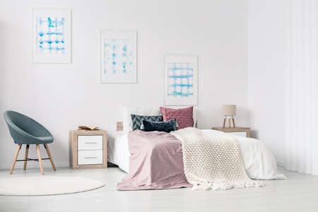 White walls bedroom interior with posters, grey armchair, bedside cabinet and a king size bed