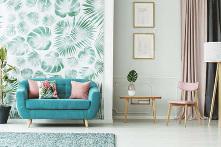 Cozy turquoise couch, wooden table and chair in a white and green living room interior with plants and leaf patterns