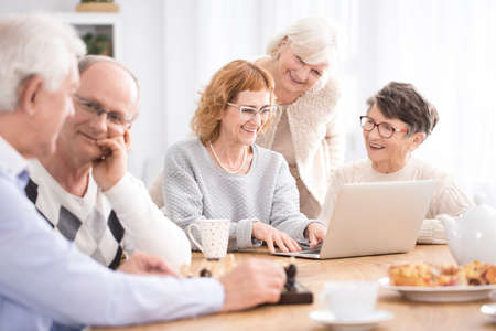 Happy seniors talking, surfing the Internet and drinking coffee together at a nursing home