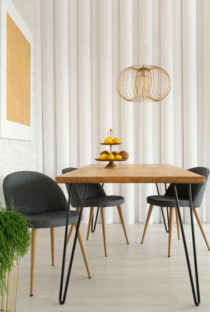 Grey chairs at wooden table under gold lamp in modern dining room interior with painting