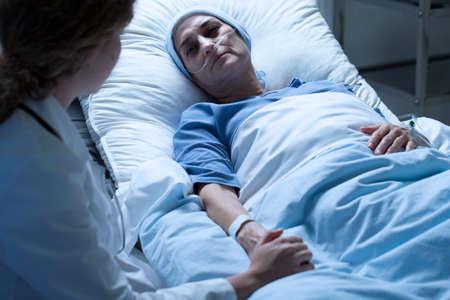 Kobieta umierająca na raka, obok niej pielęgniarka w białym mundurze Zdjęcie Seryjne