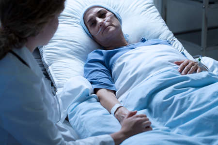 Woman dying of cancer and a nurse in white uniform next to her Stockfoto
