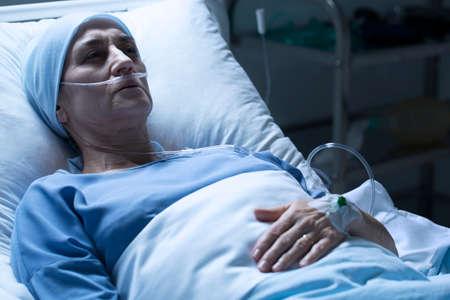 病院のベッドで一人で癌で死ぬシニア女性