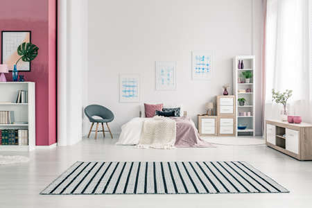 Spacious, scandinavian bedroom interior design with white walls, king size bed, wooden bookshelves and striped rug
