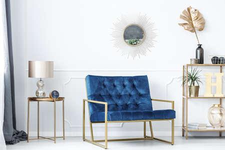 Blauwe bank tussen gouden tafel met lamp en planken met bladeren in glamour woonkamer interieur Stockfoto