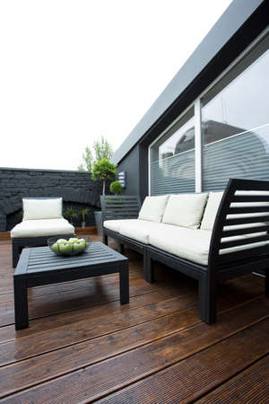 Garden furniture on terrace of apartment with wooden floor and plants