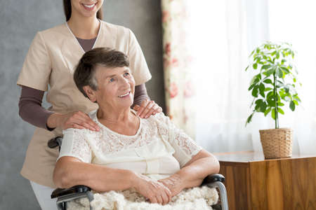Happy disabled senior woman in the wheelchair and caregiver behind her Stock Photo