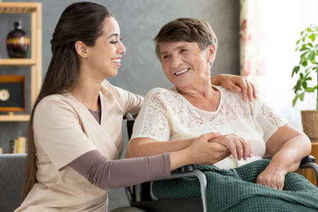 Smiling nurse supporting happy elderly woman in the wheelchair Stock Photo