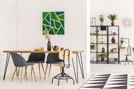 Wooden dining table, grey chairs and geometrical painting on the wall in dining room interior with a shelf in the background Banco de Imagens