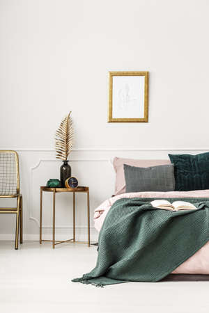 Gold table with leaf between bed and chair in green bedroom interior with mockup of poster Foto de archivo - 97699455