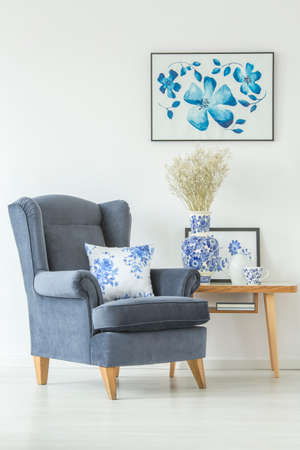 Close-up of comfy, blue armchair with a floral pillow standing next to a wooden table in white living room interior Banco de Imagens