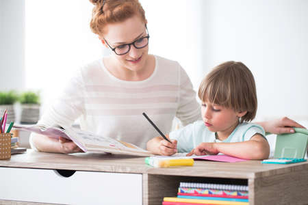 Smiling sister helping her younger brother with homework at a desk Banque d'images - 97699457
