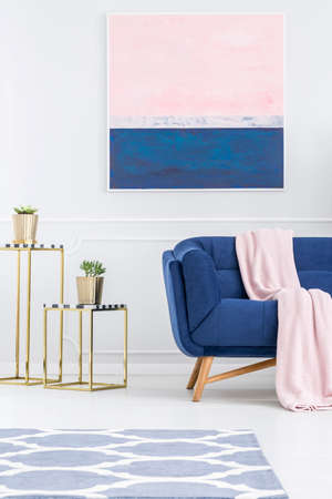 Plant on gold table in pink and blue apartment interior with couch and painting on white wall 스톡 콘텐츠