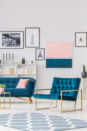 Patterned rug and navy blue armchair in living room interior with gallery of posters on white wall