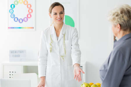 Smiling nutritionist with measure tape welcoming patient in the clinic