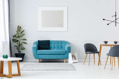 Turquoise couch against white wall with painting in flat interior with ficus and chairs at table