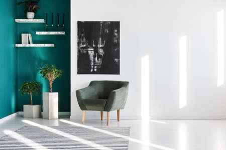 Sillón gris junto a plantas y pintura negra en la pared en el interior de una sala de estar Foto de archivo