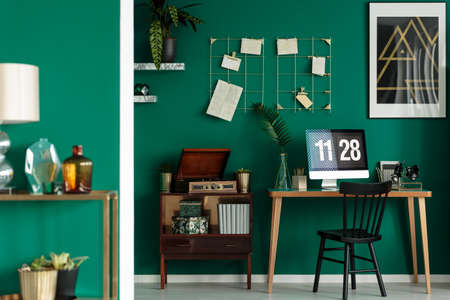Vintage home office interior with green wall, wooden desk, cabinet and black chair 写真素材