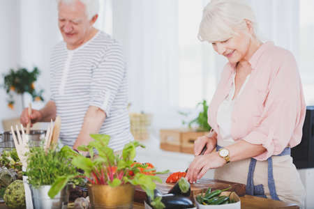 Older woman cutting a tomato for a salad in a modern, eco kitchen, preparing food with her husband