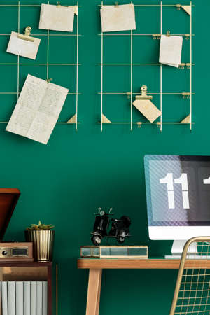 Cropped photo of a computer on a wooden desk, metal wall organizer and figurine motorcycle in home office interior 写真素材