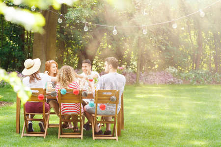 Group of smiling friends eating lunch at  a garden party Foto de archivo