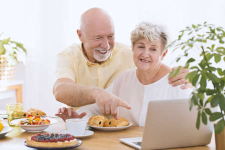 Senior couple smiling in front of the laptop sitting at a table with cake and sweet buns Фото со стока