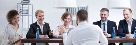 Group of smiling recruiters listening to a man with good references Stock Photo - 97752182