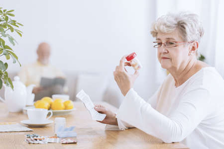 Sad senior woman sitting at the table with tablets and prescription