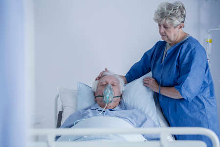 Senior woman in a hospital apron watching over her husband after a stroke