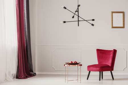 Red armchair next to a copper table, against white wall with mockup of poster in sophisticated apartment interior Banco de Imagens