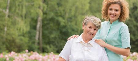 Portrait of an optimistic senior lady with her kind nurse