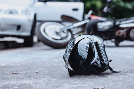 Close-up of a black biker helmet on the street with overturned motorbike in the background. Road collision concept