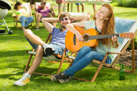 Young girl playing the guitar at a grill party with her friend listening Stock Photo