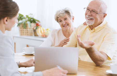 Young insurance agent with smiling couple showing an offer on the laptop