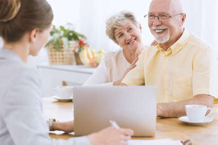 Happy seniors in front of the laptop with insurance agent writing down notes Stock Photo