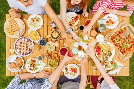 High angle of people toasting at a table with food on the terrace Stock Photo
