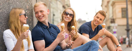 Close-up panorama of two positive couples in the city centre, eating ice cream
