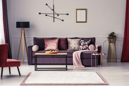 Mockup of empty poster above violet sofa with pink blanket in womans living room interior