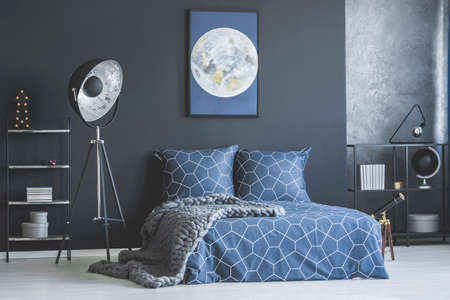 Industrial lamp next to bed with navy blue bedding against dark wall with moon poster in bedroom interior Stock fotó